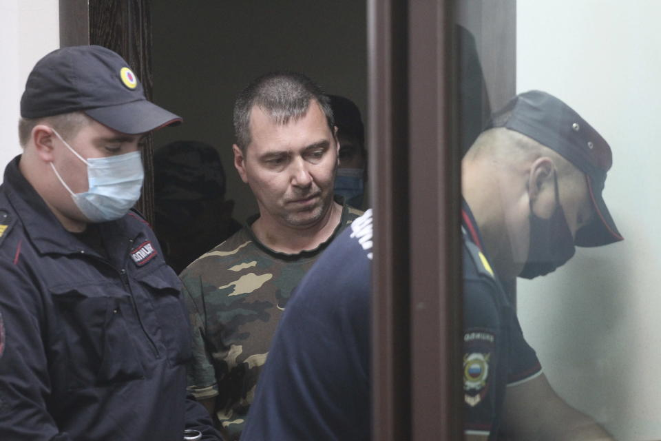 Alexander Popov, a man who was arrested on suspicion of murder and surrounded by police officers, arrives at a courtroom in the city of Gorodets, 60 km. (36 miles) north-west of Nizhny Novgorod, Russia, Sunday, June 20, 2021. A court in central Russia has arraigned the suspect on murder charges in the death of an American woman studying at a local university. The body of 34-year-old Catherine Serou was found Saturday in the woods area near the city of Nizhny Novgorod, 400 kilometers (250 miles) east of Moscow. (AP Photo/Roman Yarovitsyn)