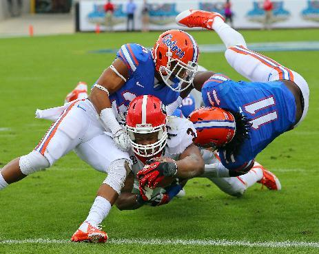 Georgia tailback Todd Gurley plows his way into the end zone between Florida defenders Cody Riggs, left, and Neiron Ball during the first half of an NCAA college football game in Jacksonville, Fla., Saturday, Nov. 2, 2013. (AP Photo/Atlanta Journal-Constitution, Curtis Compton)