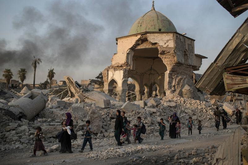 Fleeing Iraqi civilians walk past the heavily damaged al-Nuri mosque where Baghdadi declared Isil's caliphate in 2014 - Credit: AP