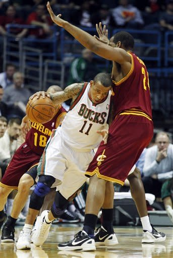 Milwaukee Bucks' Monta Ellis (11) drives around Cleveland Cavaliers' Samardo Samuels, right, during the first half of an NBA basketball game, Wednesday, April 4, 2012, in Milwaukee. (AP Photo/Jeffrey Phelps)