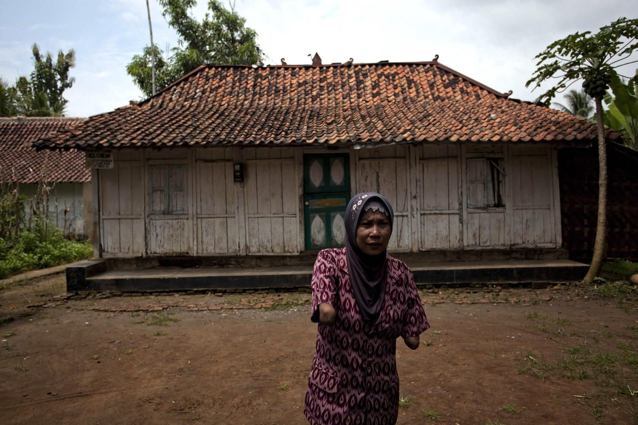 PURWOREJO, INDONESIA - MARCH 13:  Armless professional photographer Rusidah, 44, stands outside her house cum studio on March 13, 2012 in Purworejo, Indonesia. Rusidah shoots weddings and parties and has a small studio at home in the village of Botorejo, Bayan District, Purworejo, Central Java where her husband and son also reside. She has been in the photography business for nearly 20 years.  (Photo by Ulet Ifansasti/Getty Images)
