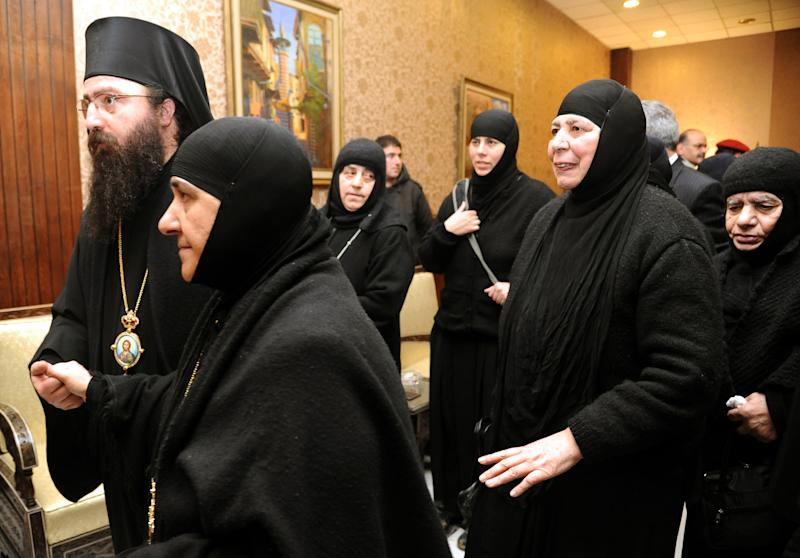 In this photo released by the Syrian official news agency SANA, a group of nuns who were freed after being held by rebels, greet church officials at the Syrian border town of Jdeidat Yabous, early Monday, March. 10, 2014. Rebels in Syria freed more than a dozen Greek Orthodox nuns on Monday, ending their three-month captivity in exchange for Syrian authorities releasing dozens of female prisoners. The release of the nuns and their helpers, 16 women in all, is a rare successful prisoner-exchange deal between Syrian government authorities and the rebels seeking to overthrow the rule of President Bashar Assad. (AP Photo/SANA)