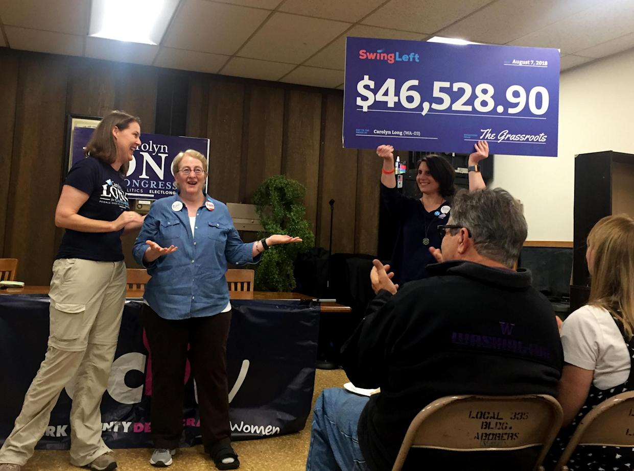 Geni Donaghey — a volunteer with Swing Left, a liberal grassroots group — presents Democrat congressional candidate Carolyn Long with a novelty check for $46,528.90 in Vancouver, Wash., on Saturday. (Photo: David Knowles/Yahoo News)