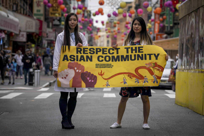 Dr. Michelle Lee, left, a radiology resident, and Ida Chen, right, a physician assistant student, unfold a banner Lee created to display at rallies protesting anti-Asian hate, Saturday April 24, 2021, in New York's Chinatown. Lee, who is Korean-born, and Chen, who is American-born Chinese, join medical professionals of Asian and Pacific Island descent who feel the anguish of being racially targeted because of the virus while toiling to keep people from dying of it. (AP Photo/Bebeto Matthews)
