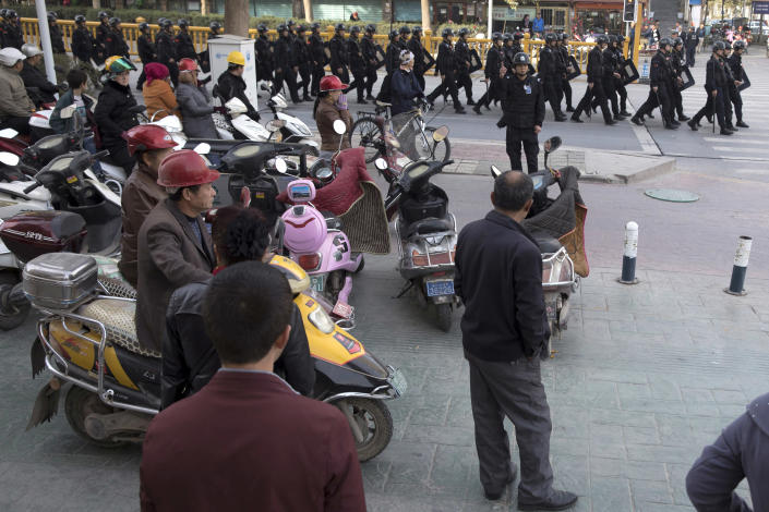 FILE - In this Nov. 5, 2017, file photo, residents watch a convoy of security personnel in a show of force through central Kashgar in western China's Xinjiang region. A Chinese Communist Party official signaled Monday, Dec. 21, 2020 that there would likely be no let-up in its crackdown in the Xinjiang region, but said the government's focus is shifting more to addressing the roots of extremism. (AP Photo/Ng Han Guan, File)