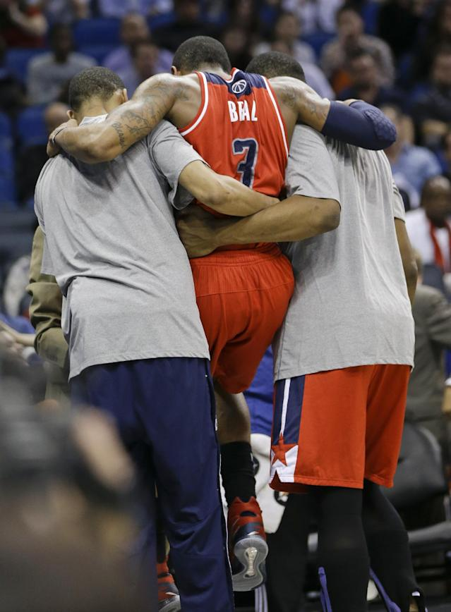 Washington Wizards' Bradley Beal (3) is carried off the court by teammates after he was injured during overtime in the Wizards' NBA basketball game against the Orlando Magic in Orlando, Fla., Friday, March 14, 2014. Washington won 105-101. (AP Photo/John Raoux)