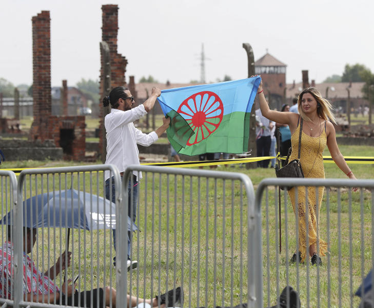 People display a Romani flag to commemorate the Roma and Sinti people killed by Nazi Germany in World War II, during ceremonies at Oswiecim, Poland, Friday Aug. 2, 2019. The American civil rights activist Rev. Jesse Jackson gathered Friday with survivors at the former Nazi death camp of Auschwitz-Birkenau to commemorate an often forgotten genocide — that of the Roma people. (AP Photo/Czarek Sokolowski)