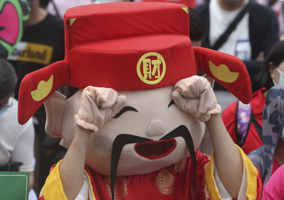A worker wearing a costume of a god of wealth pretends to be crying during a May Day rally in Taipei, Taiwan, Saturday, May 1, 2021. Thousands of protesters from different labor groups protest on the street to ask for increasing salary and securing annuity. (AP Photo/Chiang Ying-ying)