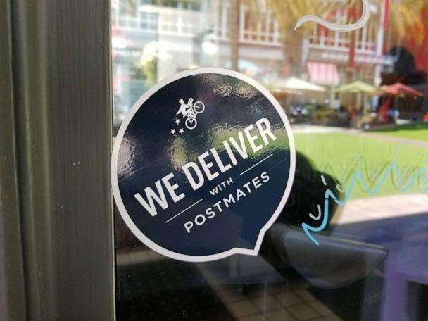 PHOTO: Close-up of logo reading We Deliver With Postmates, referencing the Postmates food delivery app service, on a restaurant window in San Jose, Calif., June 7, 2018. (Smith Collection/gado/Getty Images)