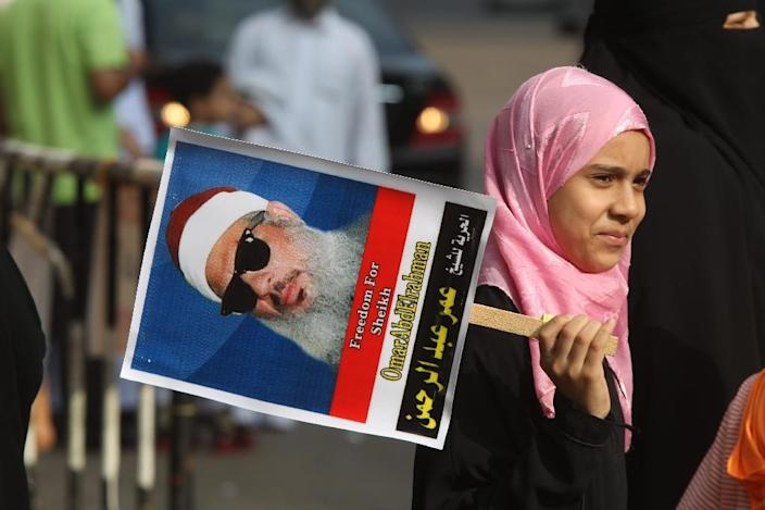 An Egyptian girl holds a portrait of Omar Abdel Rahman, who died serving a life sentence for his role in the 1993 World Trade Center bombing in New York, during a sit-in to call for his release at the U.S. Embassy in Cairo in August 2011 (AFP Photo/KHALED DESOUKI)