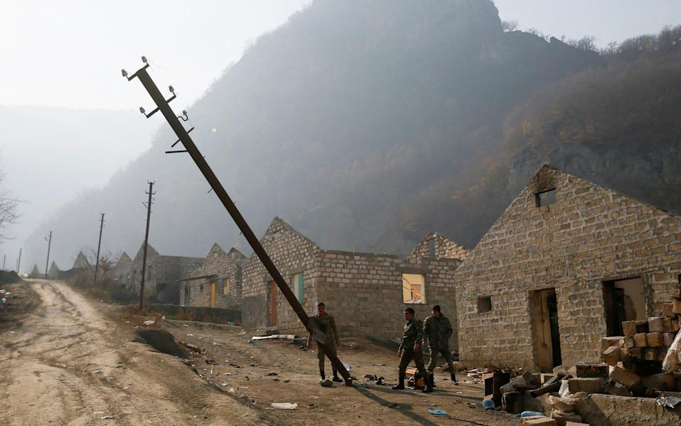 Ethnic Armenian soldiers destroy power poles in the village of Knaravan, which is soon to be turned over to Azerbaijan - Reuters
