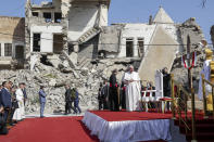 Pope Francis, surrounded by shells of destroyed churches, arrives to pray for the victims of war at Hosh al-Bieaa Church Square, in Mosul, Iraq, once the de-facto capital of IS, Sunday, March 7, 2021. The long 2014-2017 war to drive IS out left ransacked homes and charred or pulverized buildings around the north of Iraq, all sites Francis visited on Sunday. (AP Photo/Andrew Medichini)