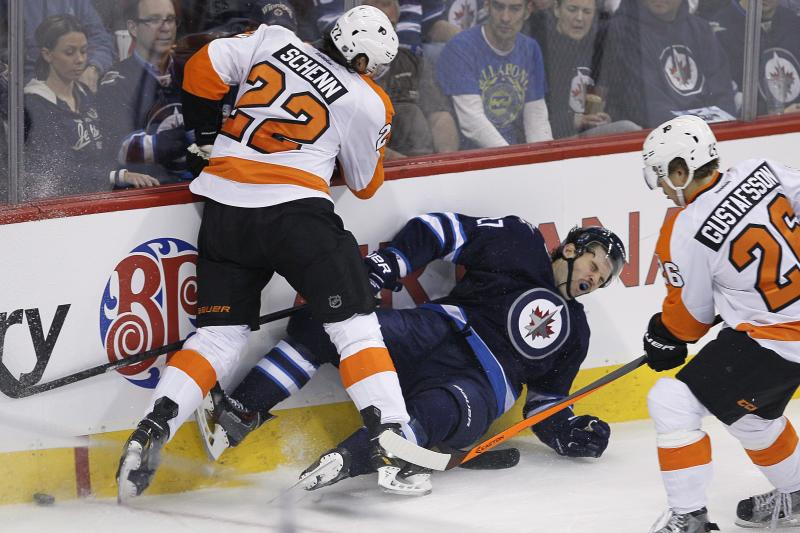 Winnipeg Jets' Eric Tangradi (27) is dumped by Philadelphia Flyers' Luke Schenn (22) as Erik Gustafsson (26) picks up the loose puck during first-period NHL hockey game action in Winnipeg , Manitoba, Friday, Nov. 15, 2013. (AP Photo/The Canadian Press, John Woods)