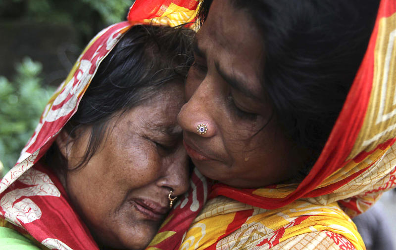 A Bangladeshi woman, left, whose relative died in a landslide is consoled by another on the outskirts of Chittagong, Bangladesh, Wednesday, June 27, 2012. Rescuers said landslides caused by heavy monsoon rains have killed at least 30 people in southern Bangladesh. (AP Photo/Anrup Titu)
