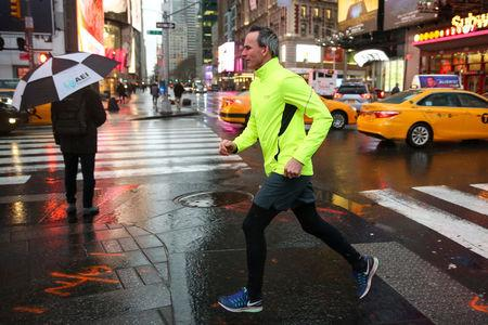 A man runs while rain falls in Times Square in Manhattan in New York, U.S., March 7, 2018. REUTERS/Amr Alfiky