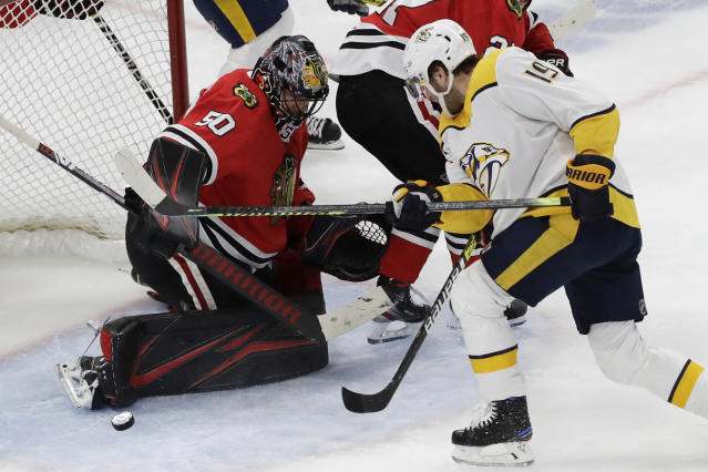 Chicago Blackhawks goalie Corey Crawford, left, blocks a shot by Nashville Predators center Calle Jarnkrok (19) during the second period of an NHL hockey game in Chicago, Friday, Feb. 21, 2020. (AP Photo/Nam Y. Huh)