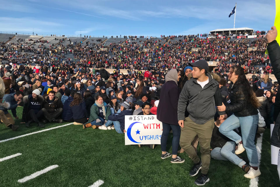 Demonstrators stage a protest on the field at the Yale Bowl disrupting the start of the second half of an NCAA college football game between Harvard and Yale, Saturday, Nov. 23, 2019, in in New Haven, Conn. (AP Photo/Jimmy Golen)