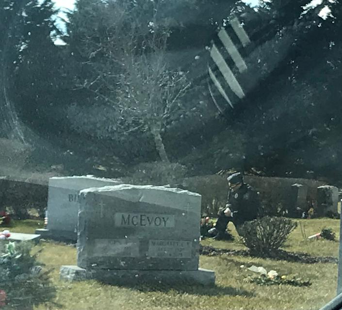 A lone man in a blue uniform kneels at the grave of Beau Biden at St. Joseph on the Brandywine church in Greenville, Delaware, on Wednesday. (Photo: Patricia Talorico/The News Journal/Imagn)
