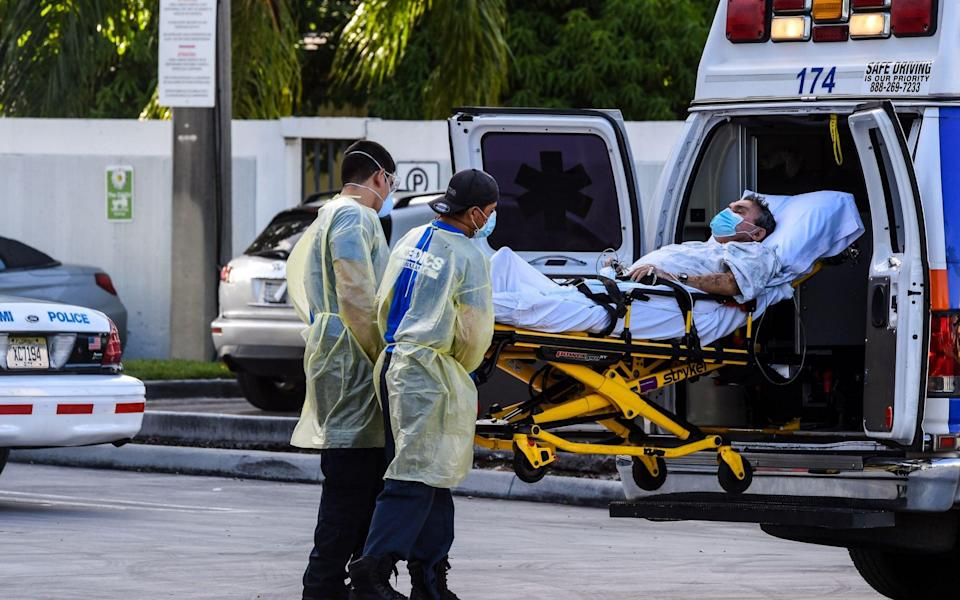 Medics transfer a patient on a stretcher from an ambulance outside of Emergency at Coral Gables Hospital where Coronavirus patients are treated in Coral Gables near Miami, on July 30, 2020. - Florida has emerged as a major new epicenter of the US battle against the disease, with confirmed cases recently surpassing New York and now second only to California. The state toll has leapt over the past week and more than 6,500 people have died from the disease there, according to health officials. More than 460,000 people have been infected with the virus in Florida, - AFP
