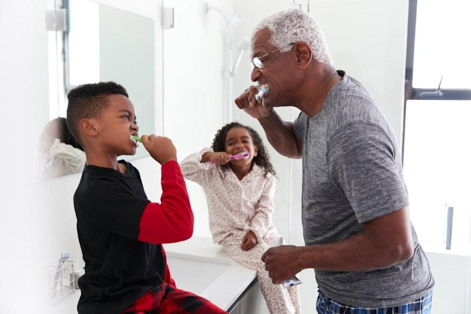 Grandfather In Bathroom Wearing Pajamas Brushing Teeth With Grandchildren