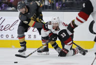 Vegas Golden Knights right wing Alex Tuch (89) and Arizona Coyotes defenseman Alex Goligoski (33) vie for the puck during the second period of an NHL hockey game Friday, Nov. 29, 2019, in Las Vegas. (AP Photo/John Locher)