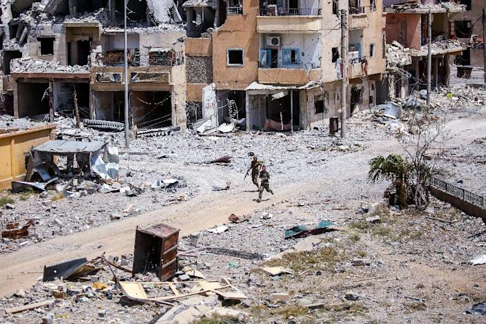 Members of the Syrian Democratic Forces (SDF) move among destroyed buildings in Raqa, northern Syria on July 28, 2017 (AFP Photo/Delil SOULEIMAN)