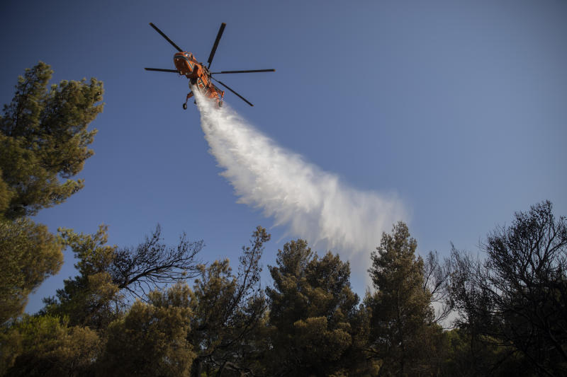 A firefighting helicopter drops water onto a wildfire in the town of Rafina, near Athens, on Tuesday, July 23, 2019. A forest fire outside Athens is threatening homes on the anniversary of a deadly blaze in the same area that claimed more than 100 lives. (AP Photo/Petros Giannakouris)
