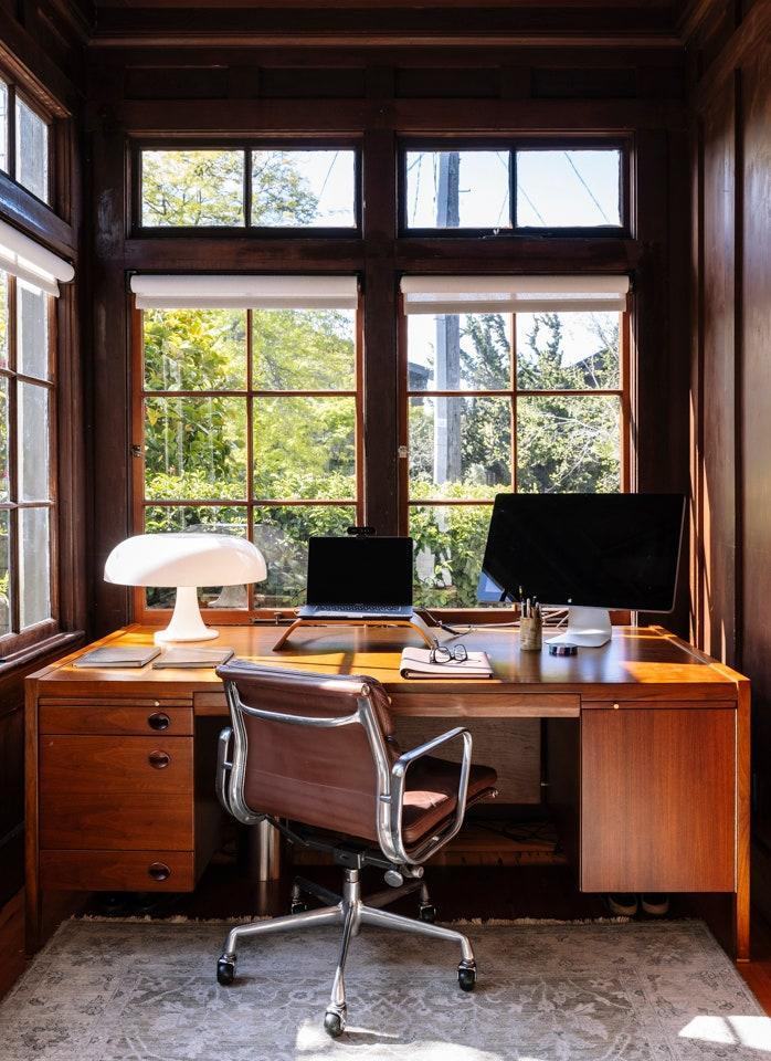"""""""I spend about 14 hours a day right here,"""" Chakrabarti says of his office, where he works from a walnut executive desk by Edward Wormley for Dunbar, and Softpad Management chair by Charles Eames for Herman Miller. The lamp is by Giancarlo Mattioli for Artemide."""