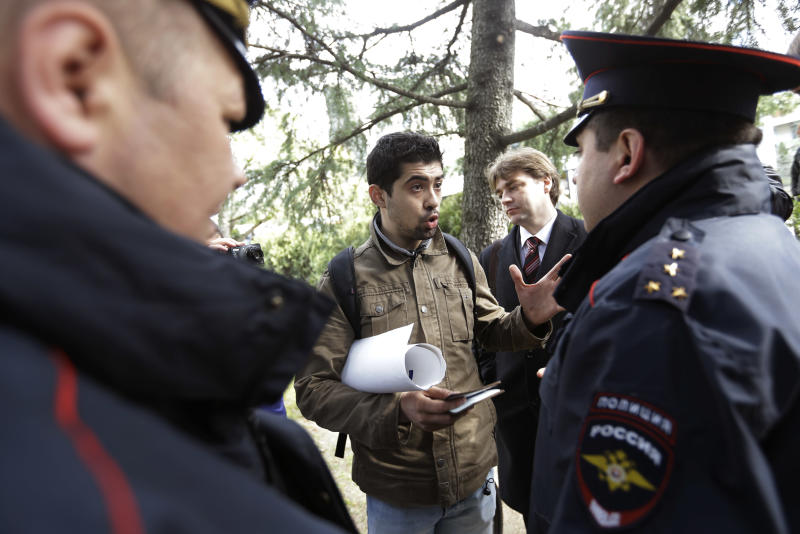 Activist David Khakim, center, talks to police officers after pulling out a banner protesting a recent prison sentence for a local environmentalist in front of the Olympic rings, Monday, Feb. 17, 2014, in central Sochi, Russia. Khakim was holding a one-man picket outside the city administration in central Sochi on Monday when two police officers took him away. Russia passed an ad-hoc law last year, banning public gatherings and rallies in Sochi during the Olympics. One-man pickets, however, are not covered by this law. Khakim was protesting the three-year prison sentence given last week to environmental activist Evgeny Vitishko for spray-painting a fence on a property in a forest where construction is banned. (AP Photo/David Goldman)