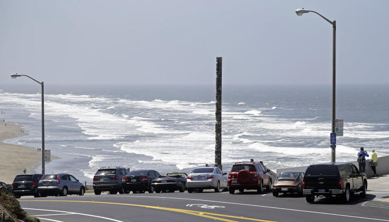 In this photo taken Tuesday, May 14, 2013 cars park for free above Ocean Beach in San Francisco. For the right to frolic in the sand, sunbathers to Southern California beaches are used to feeding the meter or paying a parking attendant. Not so along the less developed north coast where it's customary to ditch cars on the shoulder of Highway 1 to surf, swim or picnic.That sandy line that long defined California's disparate beach culture may soon fade. In search of new revenue, the state parks system is eyeing parking fees for parts of the Northern California shoreline where none existed or hiking rates to visit popular beaches south of Los Angeles during peak periods. (AP Photo/Eric Risberg)