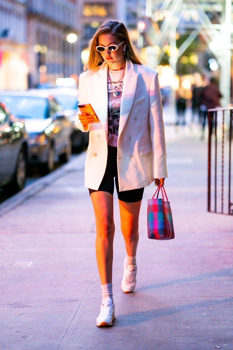 """<p>In a white blazer, a graphic tee, <a href=""""https://www.aritzia.com/us/en/product/atmosphere-short-7%22/70500.html?country=us"""" rel=""""nofollow noopener"""" target=""""_blank"""" data-ylk=""""slk:Aritzia's black Tna Atmosphere Short 7&quot;"""" class=""""link rapid-noclick-resp"""">Aritzia's black Tna Atmosphere Short 7""""</a>, white sunnies, white sneakers, and layered gold necklaces.</p>"""