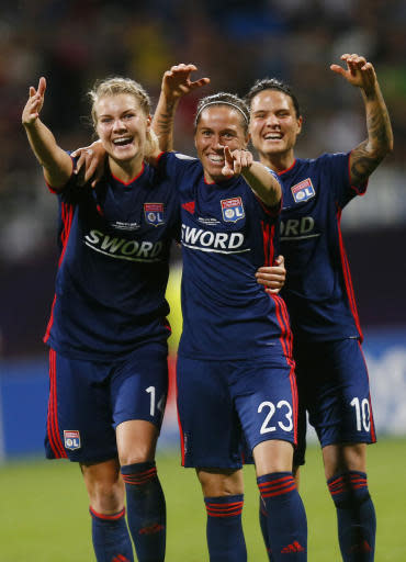 Lyon's Ada Hegerberg, left, Lyon's Camille Abily, center, and Lyon's Dzsenifer Marozsan, right, jubilate after Lyon scored during the UEFA Women's Champions League Final soccer match between Lyon and Wolfsburg at the Valeriy Lobanovskiy stadium in Kiev, Ukraine, Thursday, May 24, 2018. (AP Photo/Efrem Lukatsky)