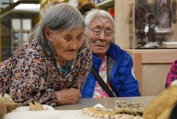 Elders in Cambridge Bay take a closer look at Inuit artefacts at the Kitikmeot Heritage Society. The society is one of a trio of northern recipients of new funding from Library and Archives Canada. (Submitted: Pitquhirnikkut Ilihautiniq/Kitikmeot Heritage Society - image credit)