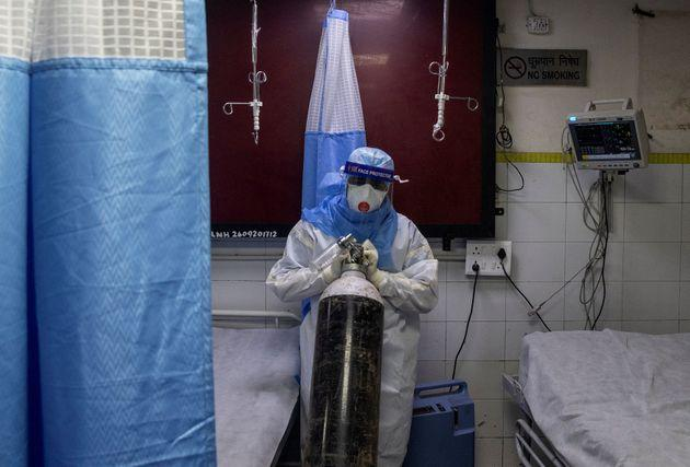 A medical worker wearing PPE pushes an oxygen cylinder at the casualty ward in Lok Nayak Jai Prakash (LNJP) hospital, in New Delhi, July 17, 2020.