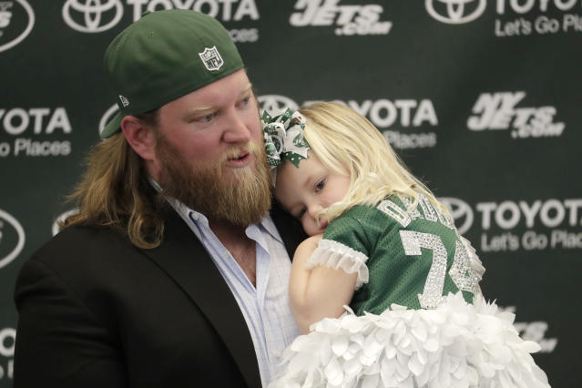 New York Jets center Nick Mangold, holding his 3-year-old daughter, Eloise, officially retires during an NFL football news conference, Tuesday, April 24, 2018, in Florham Park, N.J. Mangold announced his retirement a week earlier in a post on Twitter. He was selected to seven Pro Bowls and was twice a first-team All-Pro during his 11-year career. (AP Photo/Julio Cortez)