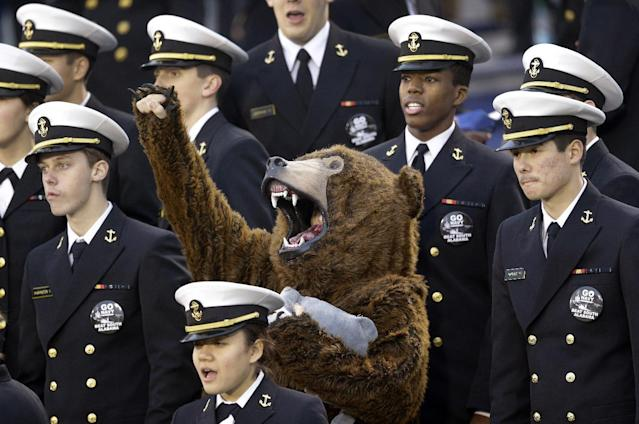 A fan dressed as a bear cheers amidst U.S. Naval Academy midshipmen in the first half of an NCAA college football game between Navy and South Alabama in Annapolis, Md., Saturday, Nov. 16, 2013. (AP Photo/Patrick Semansky)