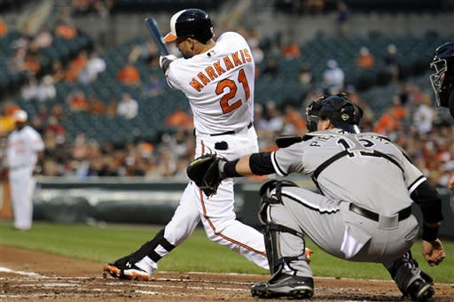 Baltimore Orioles' Nick Markakis (21) follows through on a bases-clearing double to score three runs as Chicago White Sox catcher A.J. Pierzynski watches during the second inning of a baseball game, Tuesday, Aug. 28, 2012, in Baltimore. (AP Photo/Nick Wass)