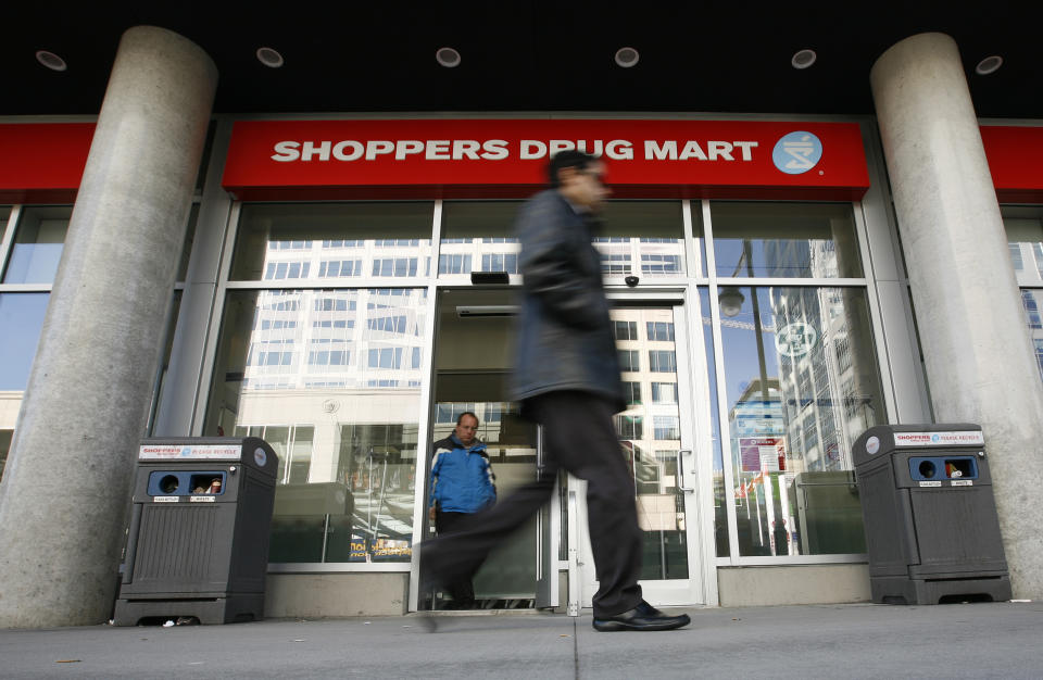 A pedestrian walks past a Shoppers Drug Mart in Ottawa November 10, 2010. Canada's No.1 pharmacy chain, on Wednesday reported a 7 percent drop in third-quarter profit and said it is facing new pressures on pricing and government reimbursement.       REUTERS/Chris Wattie       (CANADA - Tags: BUSINESS)