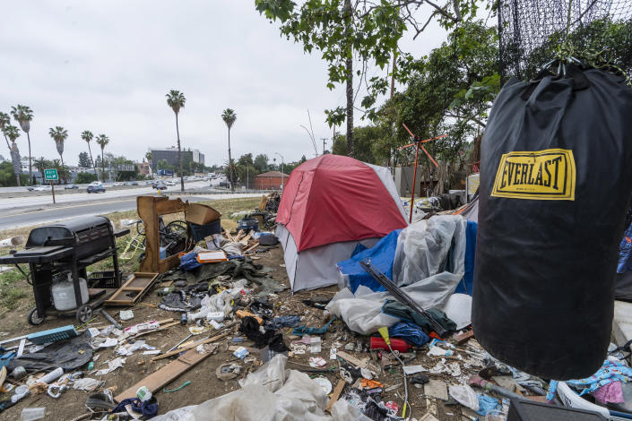 """A trashed punching bag is left at a homeless encampment is seen on the side of the CA-101 highway in Echo Park neighborhood in Los Angeles Tuesday, May 11, 2021. California Gov. Gavin Newsom on Tuesday proposed $12 billion in new funding to get more people experiencing homelessness in the state into housing and to """"functionally end family homelessness"""" within five years. (AP Photo/Damian Dovarganes)"""