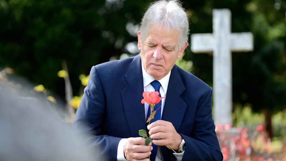 A grieving elderly man with a rose in a graveyard.