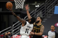 Brooklyn Nets guard Kyrie Irving (11) goes up for a shot in front of Toronto Raptors guard Fred VanVleet (23) during the second half of an NBA basketball game Tuesday, April 27, 2021, in Tampa, Fla. (AP Photo/Chris O'Meara)