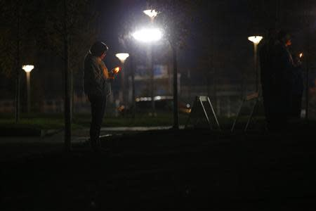 A woman stands by herself during a candlelight vigil for teacher Colleen Ritzer outside the high school where she taught in Danvers, Massachusetts October 23, 2013. REUTERS/Brian Snyder