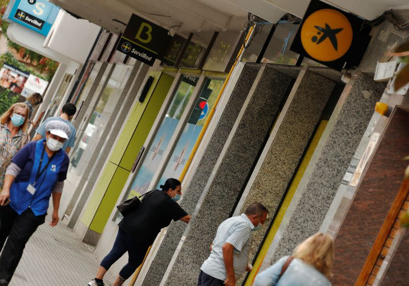 People walk past branches of Bankia and Caixabank in Barcelona