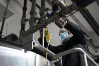 Rabbi Mendel Einhorn uses zip ties to prevent any contamination while helping Hanan Products prepare their factory for the kosher-for-passover production run, Thursday, Jan. 7, 2021, in Hicksville, N.Y. (AP Photo/Seth Wenig)