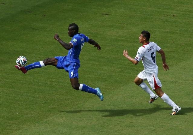Italy's Mario Balotelli takes a shot but misses as Costa Rica's Oscar Duarte (R) gives chase during their 2014 World Cup Group D soccer match at the Pernambuco arena in Recife June 20, 2014. REUTERS/Ruben Sprich (BRAZIL - Tags: SOCCER SPORT WORLD CUP)