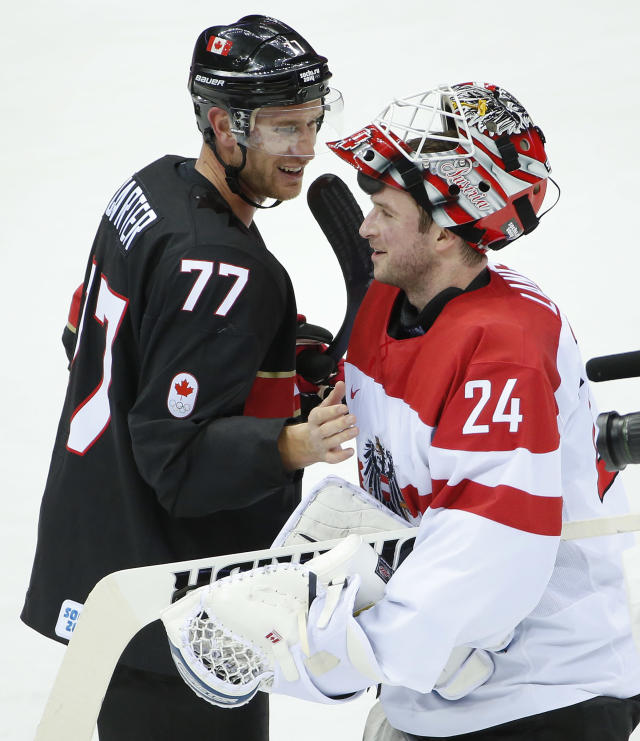 Canada forward Jeff Carter (77) greets Austria goalkeeper Mathias Lange at the end of a men's ice hockey game at the 2014 Winter Olympics, Friday, Feb. 14, 2014, in Sochi, Russia. Carter recorded a hat trick in Canada's 6-0 win. (AP Photo/Julio Cortez)