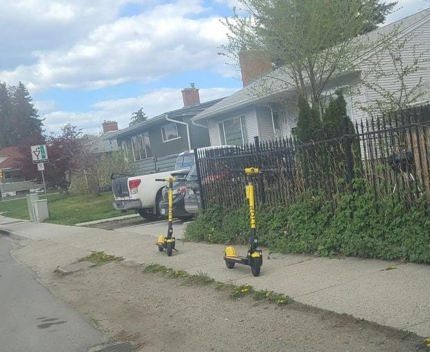 E-scooters are being left in the middle of sidewalks in Kelowna, B.C., blocking people who use wheelchairs, walkers and mobility scooters.  (Spring Hawes/Twitter - image credit)