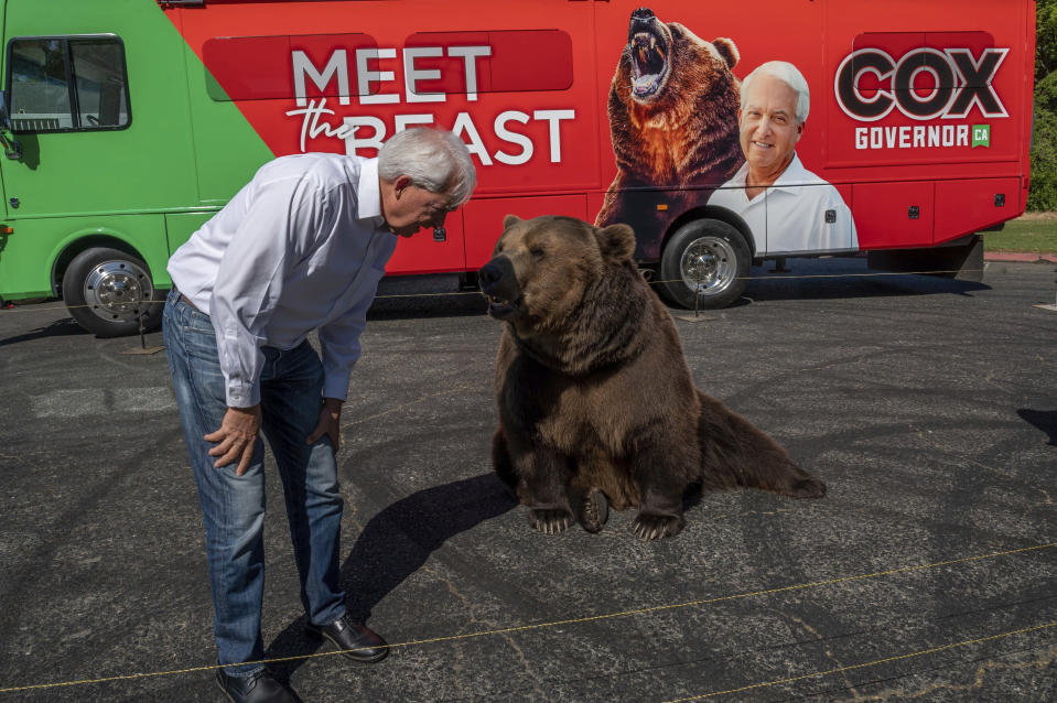 """FILE - In this Tuesday, May 4, 2021, file photo, John Cox, Republican recall candidate for California governor, begins his statewide """"Meet the Beast"""" bus tour with Tag, a Kodiak brown bear, at Miller Regional Park in Sacramento. A fading coronavirus crisis and an astounding windfall of tax dollars have reshuffled California's emerging recall election, allowing Democratic Gov. Gavin Newsom to talk of a mask-free future and propose billions in new spending for schools and businesses as he looks to fend off Republicans who depict him as a foppish failure. (Renee C. Byer/The Sacramento Bee via AP, File)"""