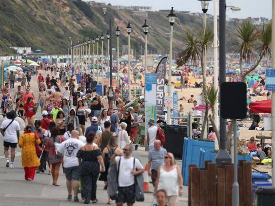People walk along the beach front on Boscombe beach in Dorset (PA)