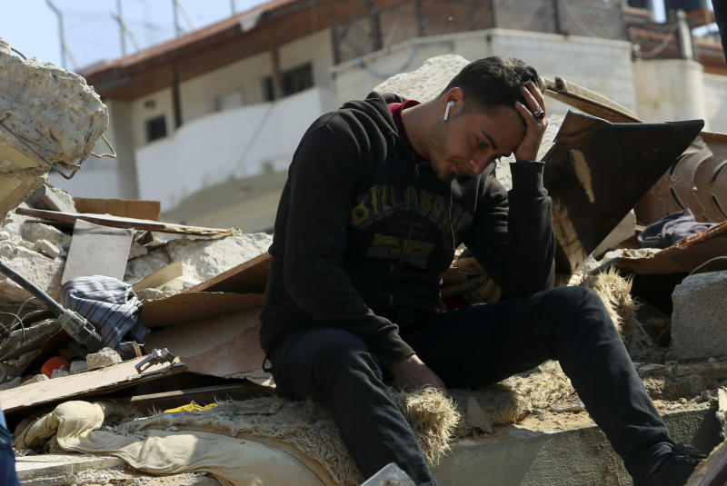 In this Wednesday, March 27, 2019 photo, Palestinian groom Walid al-Shawa sits in the rubble of a building that was destroyed in an Israeli airstrike late Monday, in Gaza City. Al-Shawa was due to get married in two weeks, but an Israeli airstrike on a Gaza City building destroyed his sister's apartment, where he had rented a second floor bedroom and had amassed everything he and his bride needed for the wedding. (AP Photo/Adel Hana)